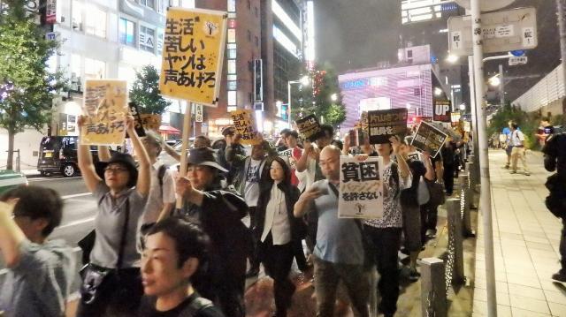 「生活苦しいヤツは声あげろ」というメッセージを掲げて歩くデモ参加者=2016年8月27日