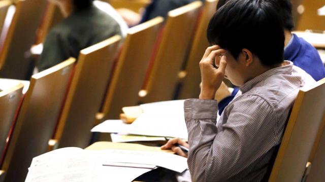 奨学金の説明会で配布資料を読む大学生