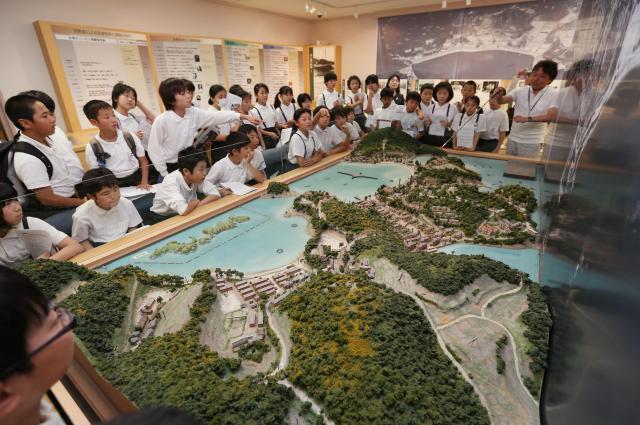 長島愛生園が立地する島の模型を前に学芸員の説明を聞く子どもたち=岡山県瀬戸内市