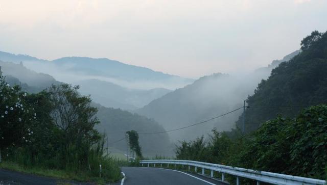 祭りが開かれる寺に向かって山道を走っていると、折り重なる山々に霞がかかっていた=岡山県美咲町