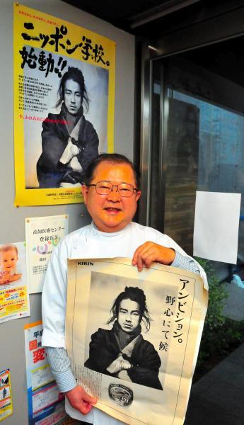 織田信福の写真が使われた広告用ポスターを手にするひ孫の英正さん=高知市升形の織田歯科医院