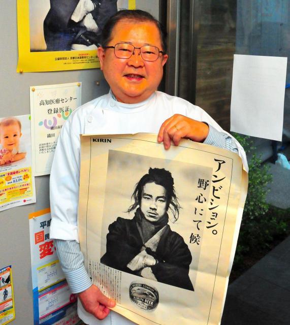 織田信福の写真が使われた広告を手にするひ孫の英正さん=高知市升形の織田歯科医院