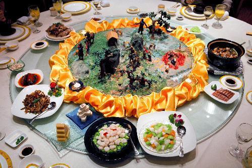 瀋陽の料理店で出された「満漢全席」の一部。清朝の始祖ヌルハチの物語をモチーフにした人形が中央の黄色い輪の中に飾られている=2007年3月26日、中国・瀋陽で