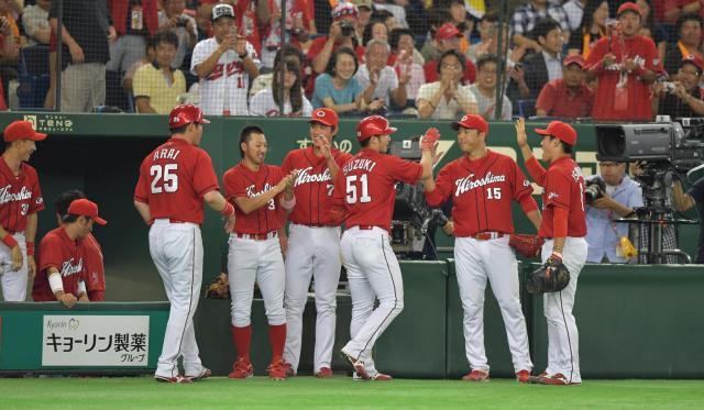 広島がリーグ優勝を決めた試合。本塁打を放って黒田(15)とタッチする鈴木(51)。新井(25)も古巣で復活した