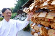 嵐ファンがかけた絵馬の前に立つ大野神社の大宮聰さん