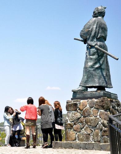 風頭公園の坂本龍馬像の前で記念撮影をする観光客ら=長崎市伊良林3丁目