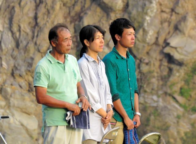 大和晃さんの遺体を収容し捜索現場を離れるヘリを見送る家族=2016年8月11日午後、熊本県南阿蘇村、後藤たづ子撮影
