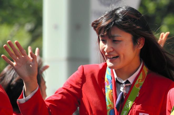 バスから手を振るレスリングの伊調馨選手(左)ら=2016年10月7日、東京・銀座、林敏行撮影