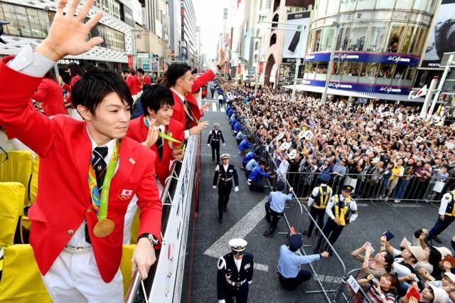 パレードで沿道に集まった大勢の人たちに手を振る体操の内村航平選手(左)ら=2016年10月7日、東京・銀座、代表撮影