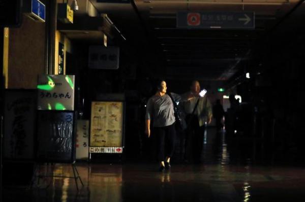 新橋駅前のビルの地下は停電し、携帯電話の明かり頼りに歩く人の姿も=12日午後4時7分、東京都港区、長島一浩撮影