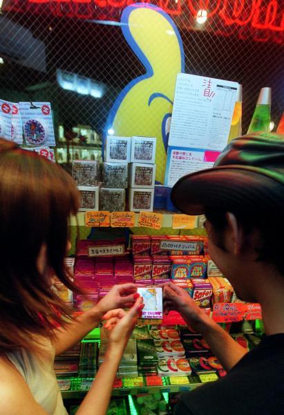 コンドーム専門店は商品を選ぶ若いカップルでにぎわう=2001年8月20日 、東京都渋谷区