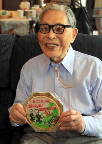 代表作「からすのパンやさん」をかたどった誕生祝いの洋菓子を手にほほえむ加古里子さん=2016年3月30日