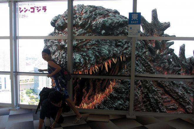 福岡タワーに登場したシン・ゴジラの巨大フィルム。逃げ惑うふりで写真を撮る人も多い=福岡市早良区