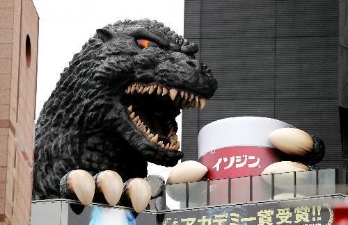 うがいアピールのため、巨大コップを持つ「実物大」ゴジラ=東京・新宿、長島一浩撮影