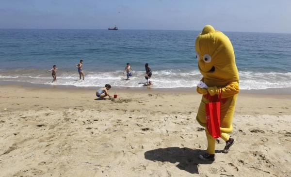 チリのバルパライソの海外で着ぐるみを着てコンドームの啓発をする男性=2015年1月、ロイター