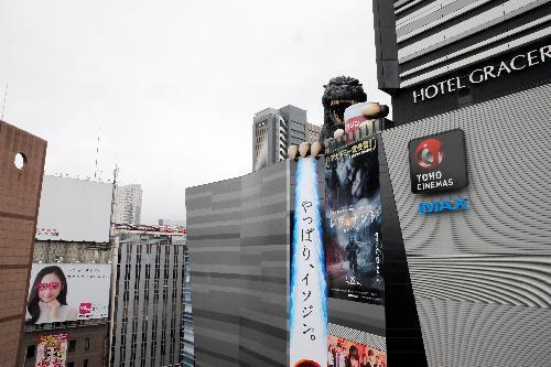 巨大コップを持つ「実物大」ゴジラ=東京・新宿、長島一浩撮影