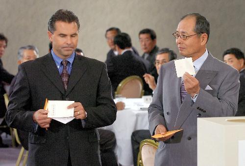 陽仲寿内野手(福岡第一)の交渉権抽選で、当たりと思ってくじを掲げるソフトバンクの王監督(右)。肩を落とす日本ハム・ヒルマン監督のくじには「交渉権確定」の文字が見える=2005年10月3日