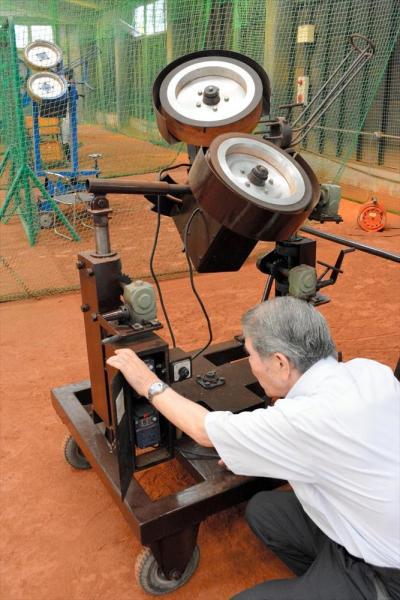 「ピッチャー再現マシン」をいろいろ調整する馬場さん。車輪の回転数を変えています。