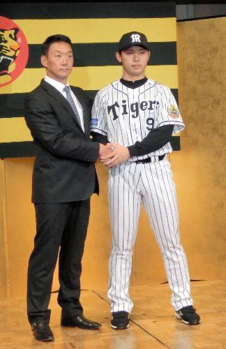 新入団選手発表で金本監督(左)と握手をかわすドラフト1位の高山=2015年12月7日