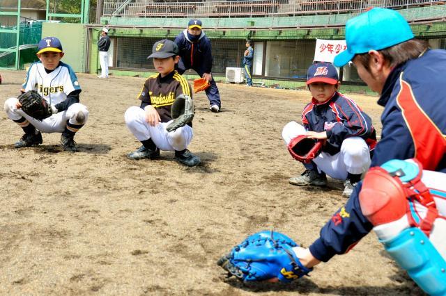 野球教室でボールの捕り方などを教わる小学生