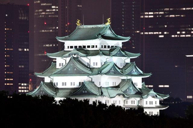 ライトアップされた名古屋城天守閣。背後はJR名古屋駅前の高層ビル群=2016年10月1日、名古屋市中区、戸村登撮影