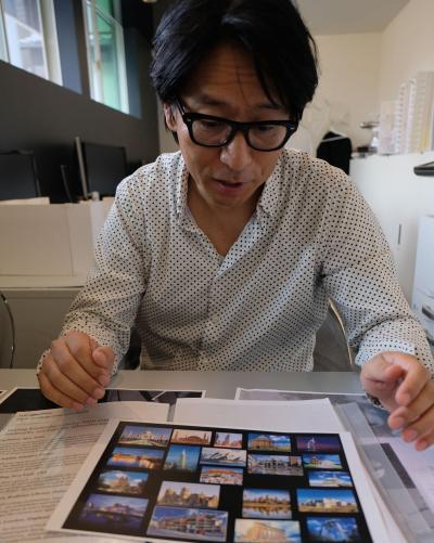 梅田スカイビルが選ばれた「世界の建物トップ20」の写真を前に説明する中谷俊治さん=東京都内