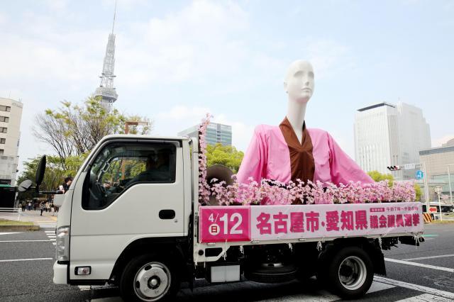 名古屋・栄を走りながら投票を呼びかけるナナちゃん人形のレプリカ。左奥は名古屋テレビ塔=2015年4月9日、細川卓撮影