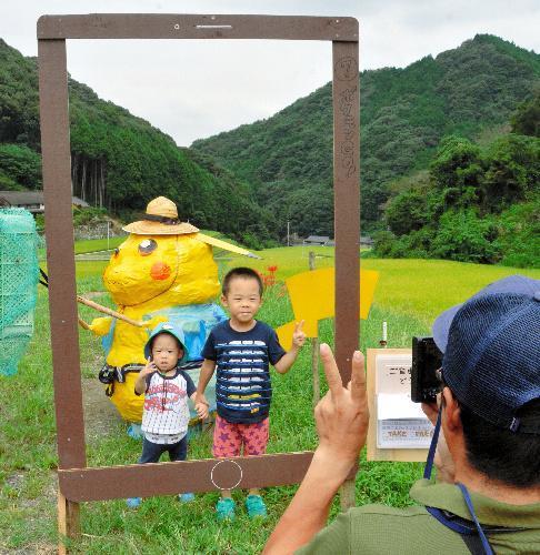「ポケモン」のかかしの前で記念写真を撮る親子=2016年9月22日、長崎県波佐見町
