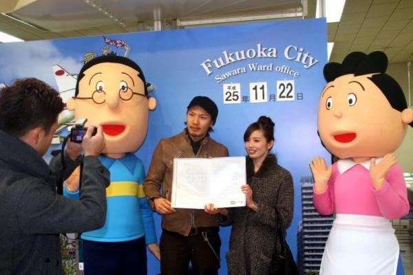 サザエさん夫婦と記念写真をする新婚さん=2013年11月22日、福岡市早良区役所