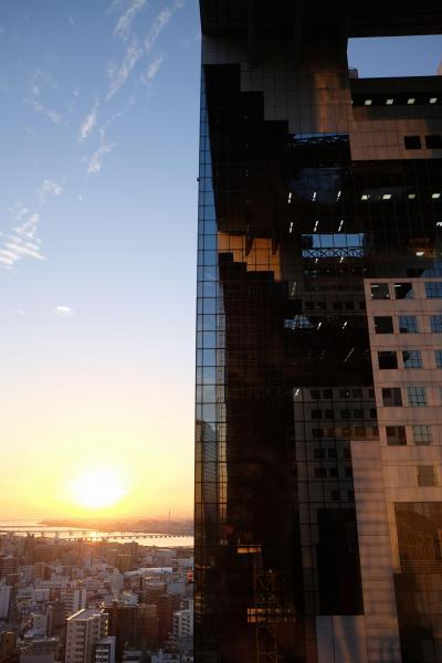 沈む夕日とビル西棟を22階から撮影。天気や光の当たり方で全く違う表情をみせる