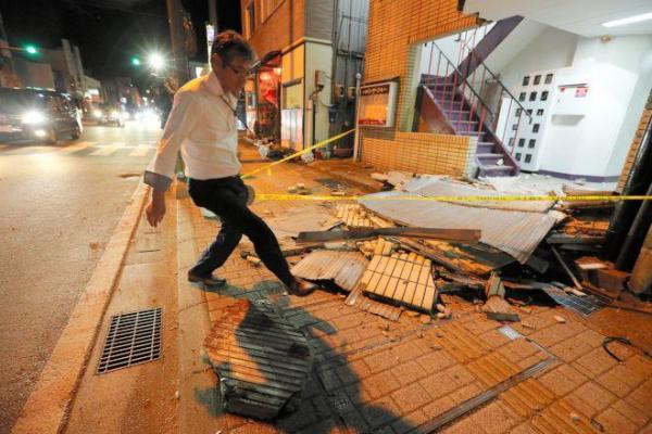 雑居ビルの壁面が崩れ、歩道に散乱した外装のタイル=21日午後6時4分、鳥取県倉吉市、橋本弦撮影