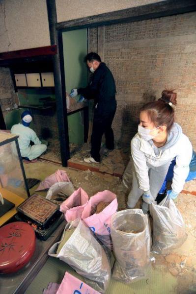 地震で崩れた室内の土壁を運び出すボランティアの人たち=23日午後2時3分、鳥取県北栄町、渡義人撮影