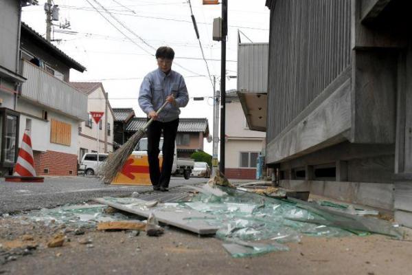 地震発生から一夜明け、割れた窓ガラスを片付ける住民=22日午前8時13分、鳥取県北栄町、小玉重隆撮影