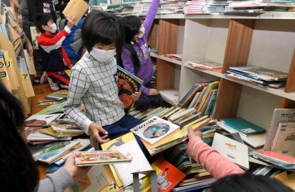 県内の公立小・中学校で授業再開。図書室で本棚から落ちた本を整理する市立成徳小学校の6年生たち=24日午前8時45分、鳥取県倉吉市、伊藤進之介撮影