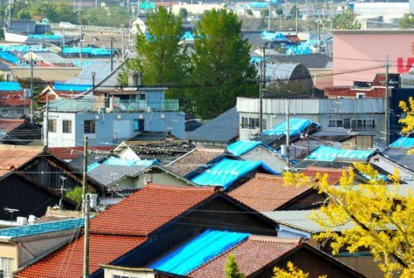 ブルーシートで屋根を覆った住宅が点在する被災地=27日午後、鳥取県倉吉市