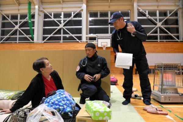 長崎県南島原市の泉川病院の医師、看護師、臨床工学技士ら9人からなる災害医療派遣チームは、倉吉市内で保健所からの要請で体育館などをまわって持病を持つ被災者を問診している。院長で循環器内科医の泉川卓也医師(右、43)は「医療チームが少ない。被害の規模は小さいが要請はあるので迅速に動きたい」と、出向いた避難所で体調不良を訴える人にも応じている=23日午後5時48分