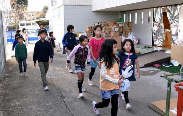 避難所となっている体育館の前を通り、登校する市立成徳小学校の児童たち。地震発生当日は校庭に避難し、そのまま下校したので、荷物を持たずの登校となった=24日午前7時59分、鳥取県倉吉市、伊藤進之介撮影