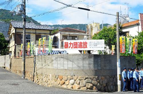 県警の特別警戒所(後方左)と「暴力団追放」と書かれた看板。左側の市道を挟んで向かい側に山口組総本部がある=2016年8月10日、神戸市灘区
