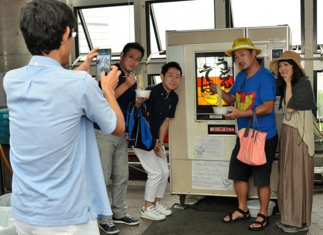 自販機の前で記念撮影をする人たち=道の駅あきた港