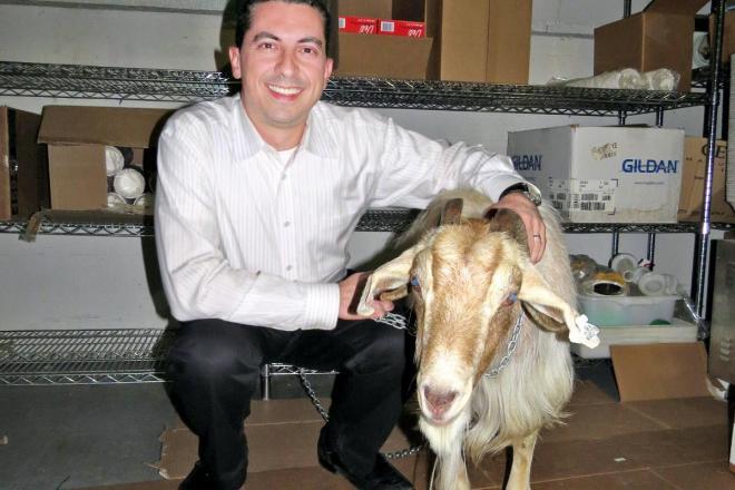 呪いをかけた先祖を持つトム・シアニスさん(左)。テレビ出演のため、インディアナ州で飼っているというヤギ「マーフィー」を店に連れてきたという