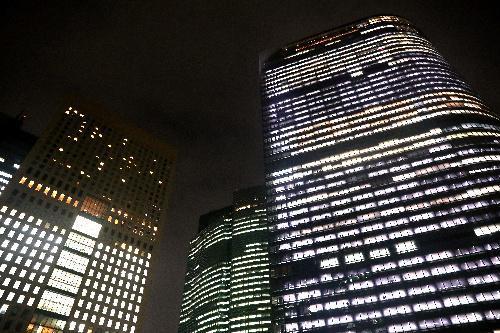 午後7時過ぎの電通本社ビル(右)。ほぼすべての窓に明かりがともる=2016年10月25日、東京都港区、林紗記撮影