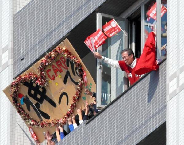 パレードをする広島カープの選手に、ビルの窓から手を振る人たち=5日午前、広島市中区、上田潤撮影