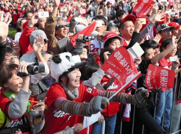 パレードをする広島カープの選手に手を振る沿道の人たち=5日午前、広島市中区、上田潤撮影