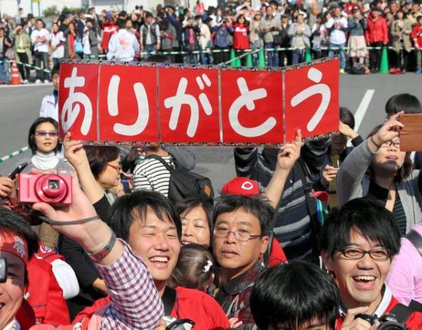 パレードをする広島カープの選手を、笑顔で迎える人たち=5日午前、広島市中区、上田潤撮影