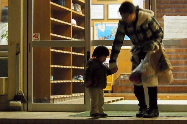 夜、職場からお母さんが大急ぎで保育園にお迎えに。「さあ、帰ろうか」=2012年12月10日、福岡市博多区