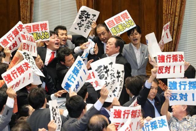 反対する野党議員に囲まれる中、安保関連法案の委員会採決をする浜田靖一委員長(中央右)=2015年7月15日