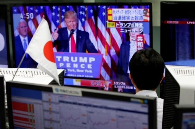 トランプ氏の勝利を伝えるニュースに見入る日本の為替ディーラー=2016年11月9日、東京、ロイター
