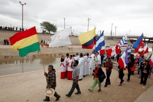 アメリカとの国境で行進するメキシコの人々=ロイター