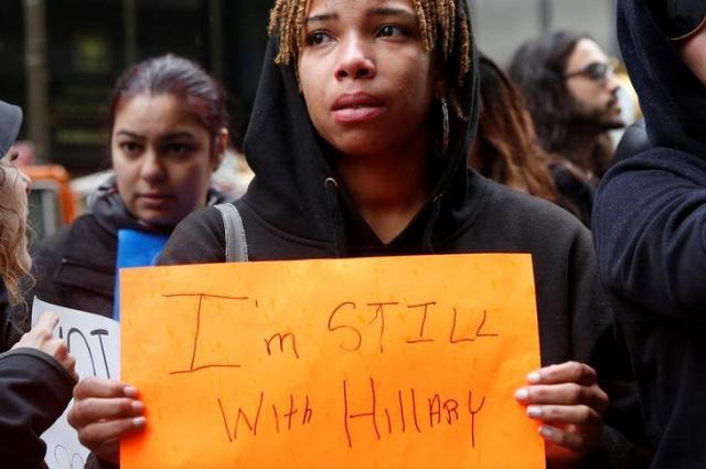 「I'm STILL WITH Hillary」と書いた紙を掲げる民主党支持者=2016年11月9日、ロイター