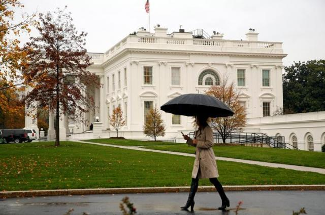 大統領選から一夜明けたホワイトハウスを歩く女性=2016年11月9日、ロイター